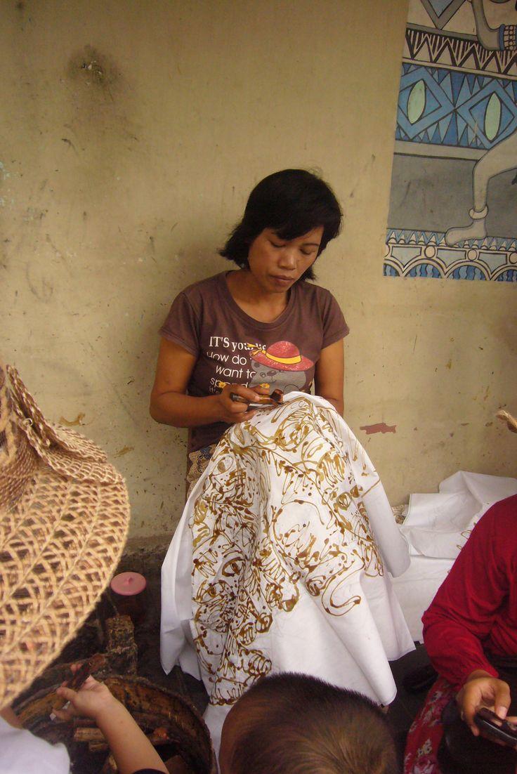 Membatik =  make batik by drawing designs in wax on cloth before dying it. As seen on Taman Sari, Jogjakarta, Indonesia.