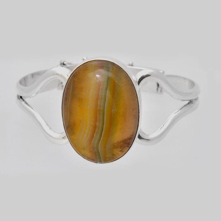 Brățară din argint realizată cu fluorit, piatră naturală semiprețioasă colorată în benzi cu tonuri de galben și verde, finisată caboșon. Dimensiuni interioare: 6x5 cm.