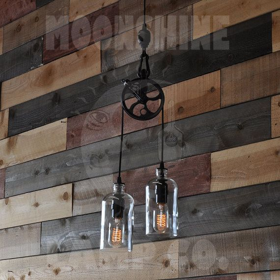 This pulley pendant lamp can be made with any two bottles of your choice, whether they be wine bottles or liquor bottles. Just let us know if you have something else in mind, other than the square bottles, pictured. The 5 round metal aluminum pulley can be finished in black, oil rubbed bronze or copper. The bottles pictured are 1L square. The fixture, from the metal ball down to the bottom of the bottles is 29. The fixture comes with two vintage style 40 watt lightbulbs. The electrical wire…