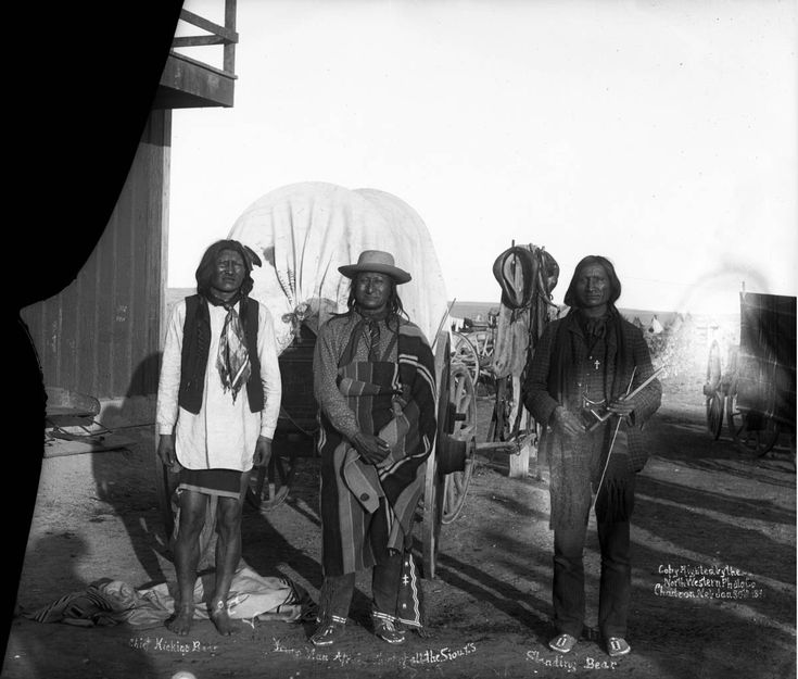 """Three Native American Sioux chiefs, leaders of the Ghost Dance, pose outside a building in front of a covered wagon, Pine Ridge Agency, South Dakota. Chief Kicking Bear, Young Man Afraid """"Chief of all..."""