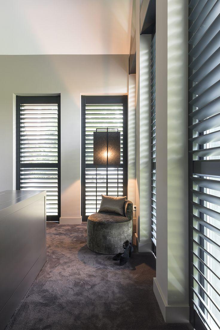"""Zowel in de slaapkamer als in de badkamer is gekozen voor houten shutters van Zonnelux. De shutters zijn op maat gemaakt en in dezelfde kleur van de raamkozijnen gespoten (RAL 7021), een zwartgrijze kleur. In de slaapkamer ligt vloerbedekking. Alle kleuren in het interieur zijn op elkaar afgestemd. Foto: Anneke Gambon – """"Stijlvol Wonen"""" - © Sanoma Regional Belgium N.V."""