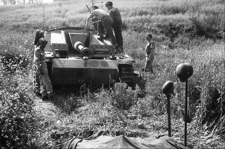 Stug, vermutlich auf der Russischen steppe.  Es sieht aus als wären es zwei gefallene Soldaten im Vordergrund zu sein.  Vom Bild ist es unklar ob die gefallenen Soldaten Teil des Stuges Besatzung waren.