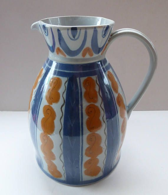 This is a very stunning and very large size stoneware jug.  It was made by Buchan Pottery, Portobello (just outside of Edinburgh), and dates to the 1950s.  It is a much more unusual design reminiscent of patterns that you might find of pieces of Poole Freeform Pottery and perhaps inspired by the Festival of Britain. It is a most stunng and harder to find larger size measuring about 10 inches in height. The diameter of the base is 7 inches. It is, of course, has no chips or cracks - and in…