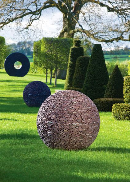 Two slate Dark Planet spheres and a slate Torus garden sculpture landscaped in a garden - David Harber  - the pebble dark planet sphere is lit from within
