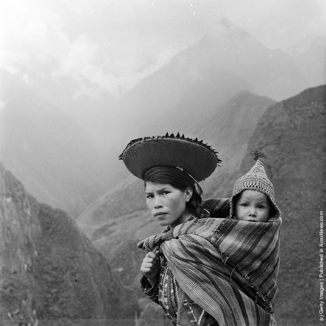 Peruvian woman treks through the Andes carrying her baby on her back in a fold of her shawl. | Photo taken in 1955.