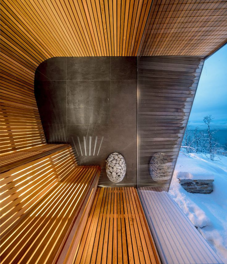 This modern house has a sauna with curved wood seating and relaxing views of the surrounding area. #ModernSauna #Windows