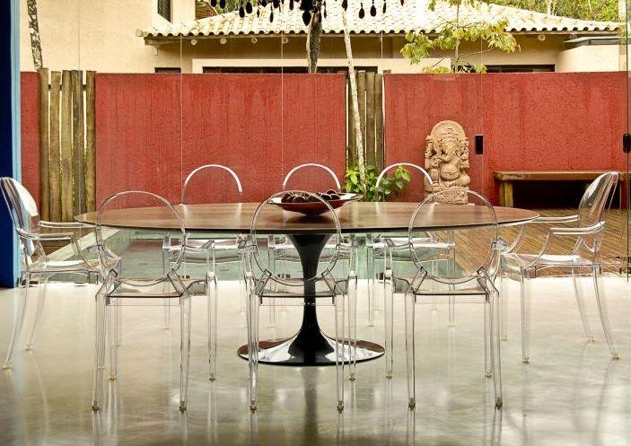 Sala de jantar com mesa Saarinen preta (ou madeira?) + cadeiras Ghost Philippe Starck + lustre preto (quase não dá para ver) + piso de cimento queimado (feito com pó de mármore pelaNS Brazil) + grande pano de vidro que faz da piscina a extensão da sala de jantar. Via Uol Casa.