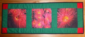 """A project in Handmade Vol 32 no 1 featuring three of my red eucalypt flower panels (12"""" panel size).  This is a Christmas table runner - just right for an Aussie Christmas! #fabricpanel www.lyndaanne.com"""