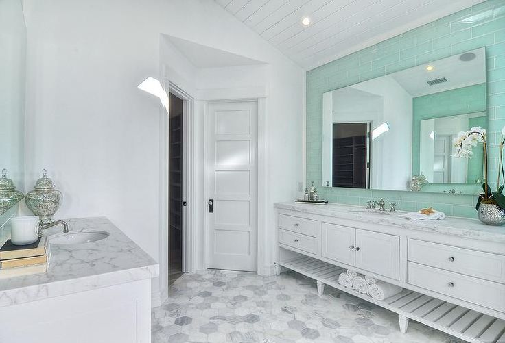 Gorgeous white and mint green master bathroom clad in large marble hex floor tiles features an eye catching wall covered in mint green subway backsplash tiles surrounding a frameless mirror mounted over an extra wide white floating washstand holding a sink with a polished vintage cross handle faucet.
