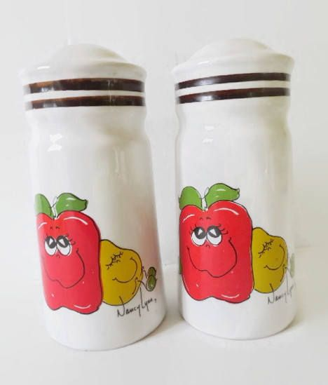Hefty 5 3/4 tall, 2 5/8 diameter ceramic salt and pepper shakers feature the delightful and iconic anthropomorphic characters of 70s designer Nancy Lynn. There are many wonderful drinking glasses, mugs, and other dishes with these fun images, but I havent found any other salt and pepper shakers available. In excellent condition with the original plastic plugs and foil Daekor label. I find no flaws in these, apart from those which were part of the manufacturing process--tiny fleabite...