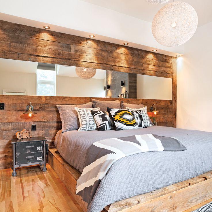 S'étendant d'un bout à l'autre du mur, la tête de lit a été construite en véritable bois de grange brun. Les propriétaires ont choisi les planches une à une pour s'assurer d'obtenir les teintes qui s'intégreraient le mieux au décor. Grâce aux luminaires encastrés dans la retombée, chaque détail du bois est mis en valeur. Le long miroir qui traverse le mur crée un effet de profondeur qui agrandit visuellement la pièce.