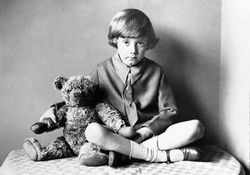 The boy in this picture is A. A. Milne's son, Christopher Robin Milne. Yes, he is the basis for the homonymous character in Milne's Winnie The Pooh. And, you guessed, that is the actual Winnie the Pooh teddy bear.