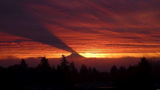 La sombra de una volcán (en las nubes) Normalmente la luz del cielo incide sobre una montaña y su sombra queda en el suelo.  En condiciones excepcionales de luz ocurre al revés.  Esta imagen fue tomada en el Monte Rainier (E.E.U.U.) al amanecer. Los primeros rayos del sol llegan a la montaña desde el horizonte y crean una sombra en las nubes que hace parecer  al Monte Rainer un volcán humeante; lo que en realidad es, aunque su última erupción ocurrió en 1894.