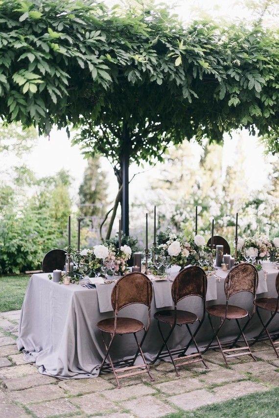 Italian villa destination wedding, reception tables under a lush garden arbor
