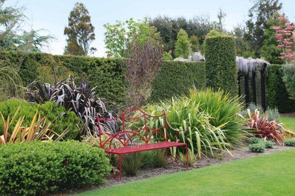 The New Zealand border, featuring various phormium, with Podocarpus cunninghamii hedging and pillars.