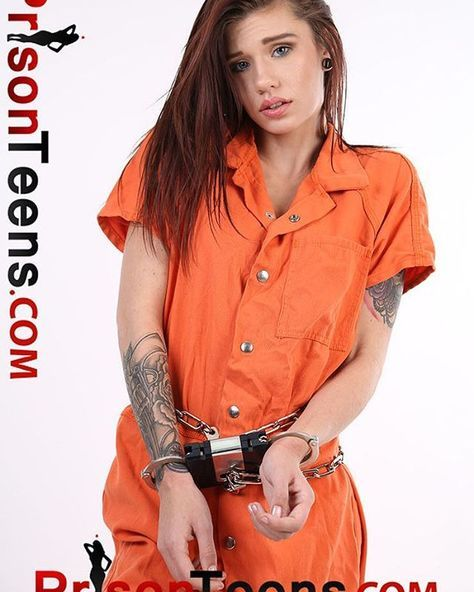 Woman poses in prisoner's outfit hands cuffed connected to belly chain with a blue box to prevent her opening the handcuffs.