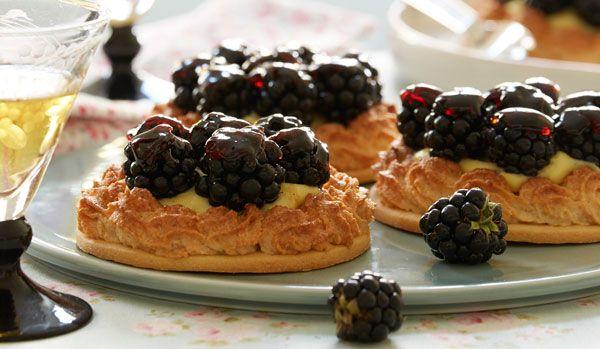 Små lækre brombærtærter med kagecreme, friske bær og lidt gelé på toppen. Uhmm... De er slet ikke til at modstå og er du ikke lige til brombær, kan du sagtens udskifte bærene med dine yndlings.