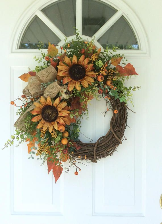 Summer Wreath-Fall Door Wreath-Sunflower Wreath-Rustic Wreath-Country Wreath-Farmhouse Decor-Cottage Wreath-Harvest Wreath-Autumn Wreath This little sunflower wreath has a rustic, country feel. Two large golden sunflowers are surrounded by an array of autumn finds, including berries with mini pumpkins, autumn foliages, cascading silver gray leaves and other greenery. A homespun burlap bow fits the look perfectly. Approximate dimensions: 22 H x 18 W x 6 D (measured tip to tip) This Reginas...