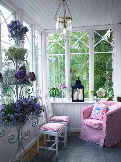 Another enclosed porch..A tiered plant stand and small patterned upholstered chairs make this a sweet retreat.
