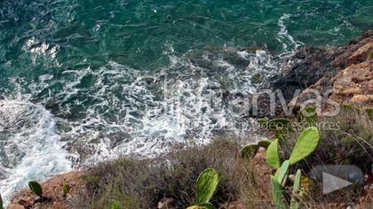 Stock video for sale at ClipCanvas: View from above of the waves slamming  the shore, Porto Azzurro, Elba Island, Italy.