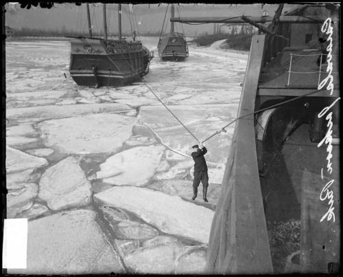 A man holds on to a rope stretched between two caravels above frozen Lake Michigan. Want a copy of this photo?  > Visit our Rights and Reproductions Department and give them this number: DN-0056498. Connect with the Museum