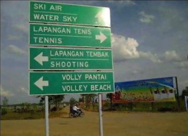 Di kawasan Jakabaring Sports Center Palembang yang menggelar event SEA Games XXVI, tegak sebuah papan penunjuk arah dwi-bahasa, Indonesia dan Inggris.     ski air = water sky (=water ski).   voli pantai (=volly pantai) = volley beach (=beach volleyball)