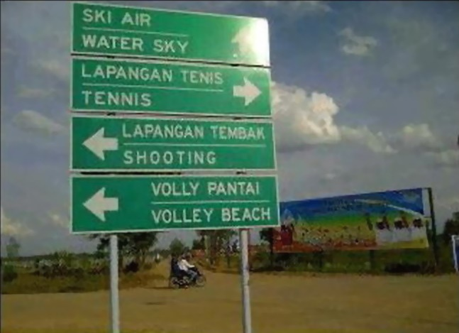 Di kawasan Jakabaring Sports Center Palembang yang menggelar event SEA Games XXVI, tegak sebuah papan penunjuk arah dwi-bahasa, Indonesia dan Inggris.     ski air = water sky (=water ski).   voli pantai (=volly pantai) = volley beach (=beach volleyball)