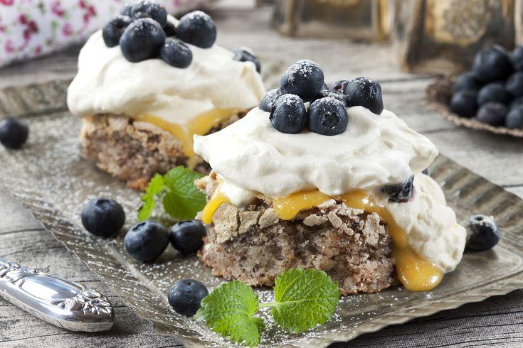 Bakelyst.no: En god nøttebunn i langpanne kan serveres sammen med mye godt. Her er nøttebunnen i selskap med sitronkrem, pisket krem og blåbær.