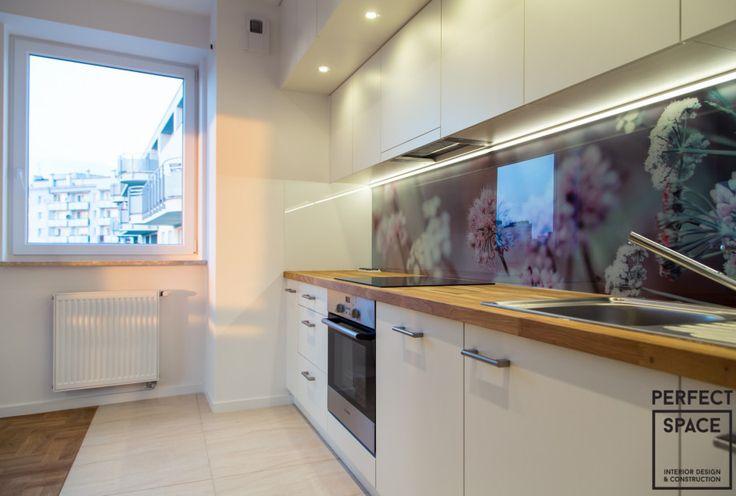 Otwarta kuchnia w nowoczesnym stylu. Drewniany blat kuchenny, białe fronty szafek, oświetlenie LED oraz backsplash z kwiatowym motywem. Strefowananie za pomocą podłogi wyznacza granicę kuchni.