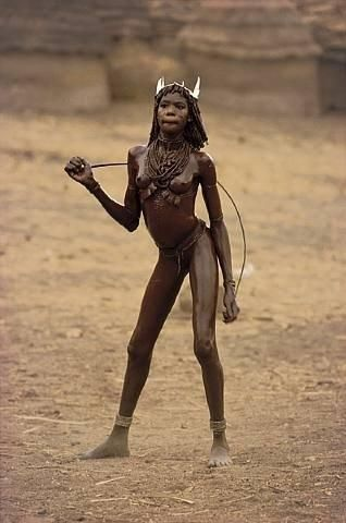 (2) THE NUBA OF KAU : Their masks, knife bouts and love dances, their extravagant paints reminding of »living Picasso paintings« do not exist with any other primitive people on earth in this form and diversity. | Nuba girl of Kau, Sudan. Photo by Leni Riefenstahl, 1970's