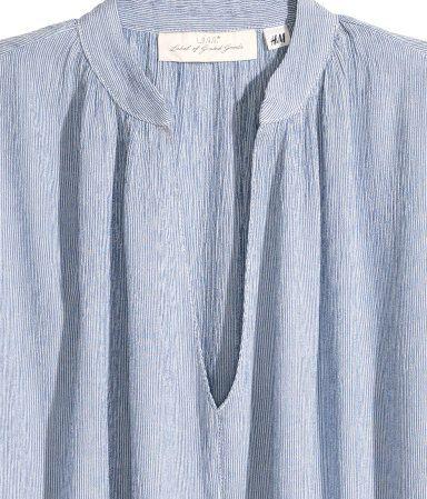 Lichtblauw/gestreept. Een wijde blouse van geweven kwaliteit met een licht…