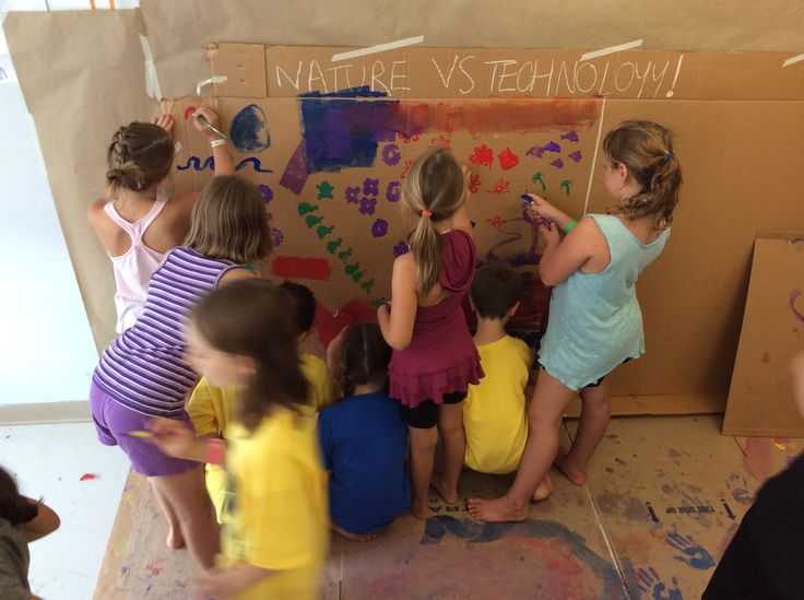 The campers working on their nature vs. technology temporary mural using foam stamps, paint brushes, foam rollers, markers and their fingers!
