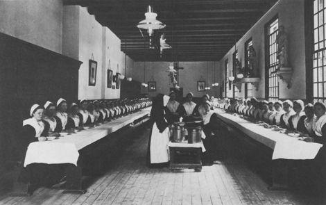 Maagdenhuis de eetzaal in 1912 (sm) (Bot). Rechts de vijf ramen naar de binnenplaats, links de kastjes voor de kinderen en de rookkanalen van bakkerij en keuken. Ten behoeve van de foto is de opstelling in de eetzaal kennelijk gewijzigd. De meisjes die aan de binnenzijde der tafels zaten zijn naar de buitenkant verplaatst, de tafels zijn tegen elkaar geschoven. #NoordHolland #Amsterdam #wezen #katholiek