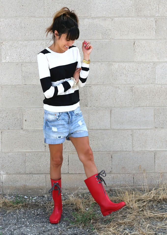 Pair denim shorts with rubber boots and a light sweater. The look is cute and rain-ready.