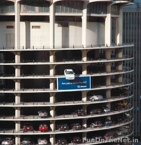 Allstate Insurance: Marina Tower  Yes, that is an actual car placed on the edge of the parking garage. It is an advertisement to promote Allstate auto insurance in Marina Towers, a famous landmark in the center of downtown Chicago.