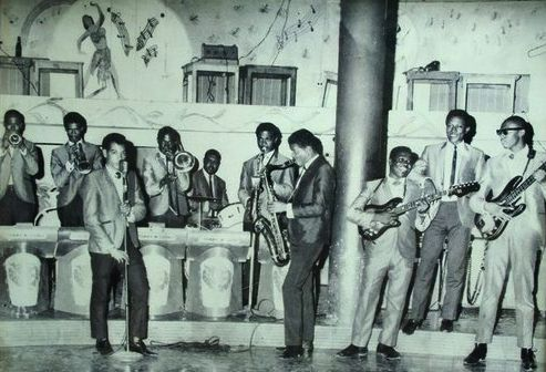 "TOMMY McCOOK THE SUPERSONICS: Lester Williams, Johnny Moore, Danny Simpson, Lloyd Knibb, Herman Marquis and Lloyd Delpratt. On the floor from left to right, Kes Chin, Tommy McCook, George Tucker and Clifton ""Jacky"" Jackson..."