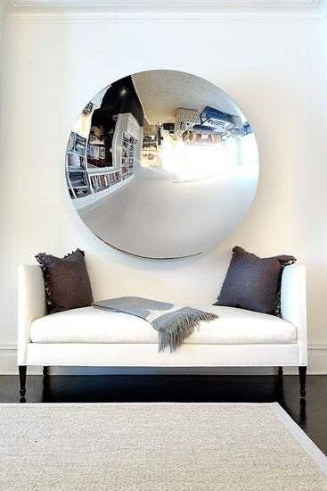 Chic, minimal foyer design with gorgeous white settee with gray purple linen pillows and gray cashmere throw and round mirror.