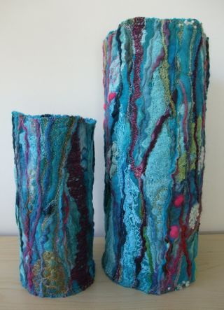 Handmade felt of merino wool, yarns and hand-dyed scrim. Embellished with machine and hand embroidery then stitched into vase wraps. 45cm + 30cm tall.
