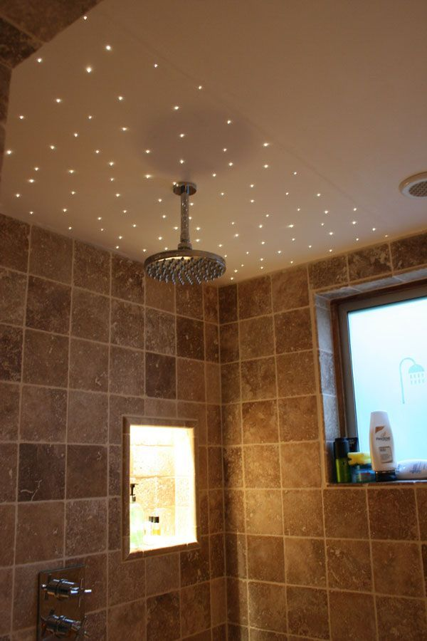 Fibre optic lighting is perfect for shower enclosures since there is no electricity in the glowing points around this wet room shower head