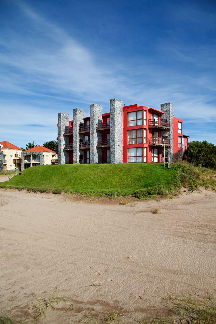 Fachada en piedra de hotel de bosque y playa: Gris y rojo.