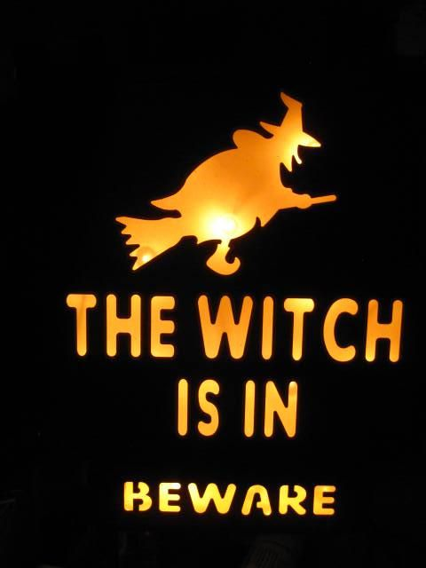 """Halloween""""The Witch Is In"""" Metal Lighted Sign.The electric signmeasures approximately 12"""" high & about10"""" wide x 2"""" deep.There is a large metal hoop for hanging. When you add the metal..."""