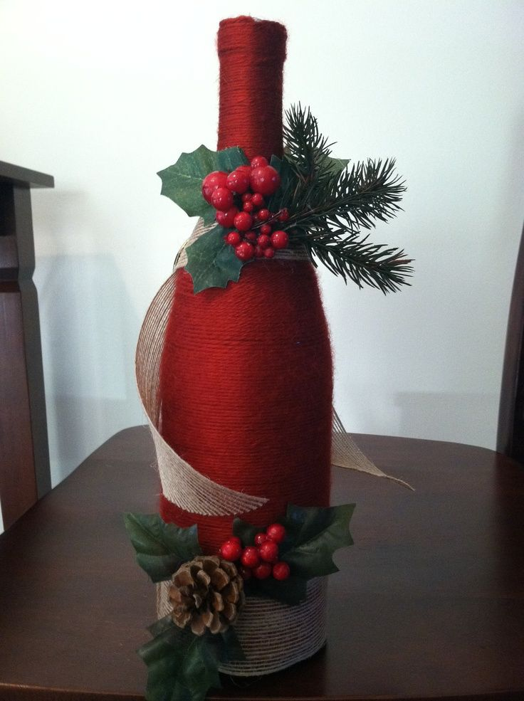 A wine bottle wrapped in yarn with some christmas decor