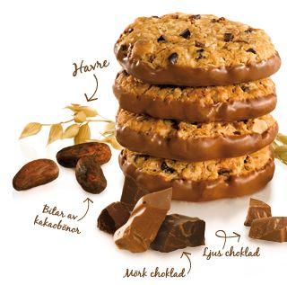 Baka Christinas Chokladbegär  (ca 20 kakor)    5,5 dl havregryn  4 dl vetemjöl  150 g smör eller margarin, rumstempererat  3/4 dl farinsocker  1/2 dl socker  1 dl ljus sirap  2 dl mörk choklad, grovhackad  3/4 dl kakao nibs  2 tsk bakpulver  1/4 tsk salt  3/4 tsk rivet apelsinskal  1/2 dl vatten  Ljus choklad för doppning, minst 400 g    * Om du inte hittar några Nibs kan du använda fint hackad riktigt mörk choklad (minst 70 % kakao) istället.    1. Förvärm ugnen till 200 °C. Blanda mjöl…