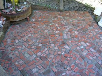 "This brick patio was made from left over and recycled bricks, the main bulk of which were off-cuts from a ""herring bone"" driveway. The herring bone pattern, at a 45 degree angle, leaves an excess of triangles and diamonds when finished. The use of such shapes created a stained glass look for this patio, something that would have been very labor intensive otherwise."