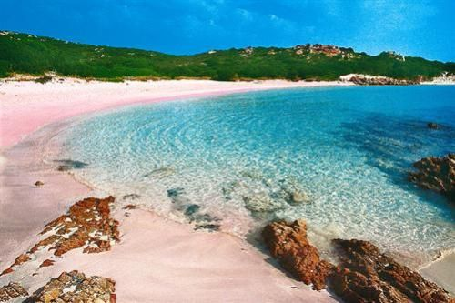 Pink Beach La Maddalena Archipelago, North-East Sardinia. The Pink beach stands in Budelli, one of the islands of the Archipelago; Budelli has an area of just 1.6 square kilometres. The beach takes name from the particular pink coral colour of the sand, due to the numerous shells and little fragments of red corals.