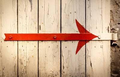 Roter Pfeil, entdeckt an einem Garagentor, in eine Richtung weisend. Nach Osten! Symbolhaft? Oder nur einfach nach rechts zeigend. Eine geschmückte Torangel wurde liebevoll verschönert: Die Pfeilspitze hat Schwung, sie wechselt das Material, ist gemalt von Metall zu Holz, oder umgekehrt? Das Ende des Pfeils trifft genau die überlackierte Schraubenm...