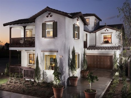 A two-level porch below a brown tile roof brings the outdoors in. A third story rises from the center of this classic stucco home. New homes by Ryland Homes in Chino, CA.