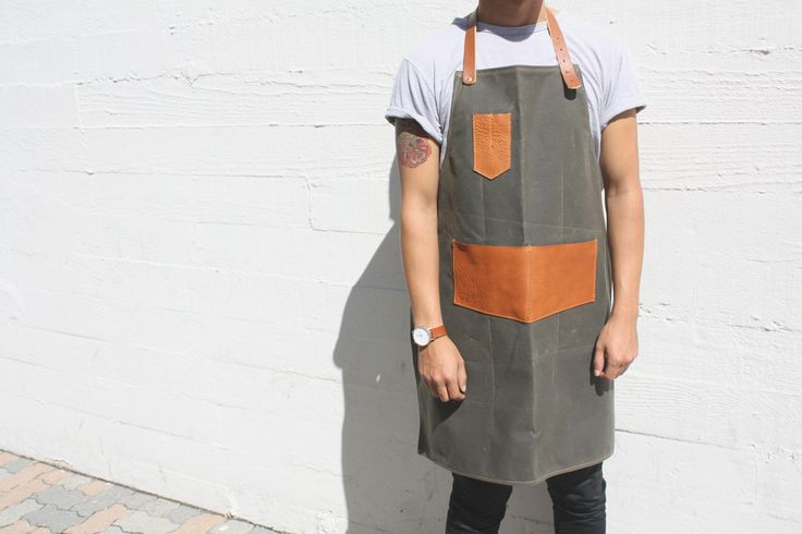 """This handmade waxed canvas and leather apron is as utilitarian as it is eye catching. This full cover style is great for keeping your clothes clean while getting your hands dirty. Hold your cookware, tools, or gardening gloves in the oversized leather pockets that will just improve with age. A great gift for the craftsman.  Dark Olive Waxed Canvas 5-6oz Latigo Leather 32.75"""" L x 29"""" W Adjustable Leather Waist Strap Hand Made Copper Rivets 2 Pockets Measuring 7"""" x 5.5"""" 2 Pockets Measuring…"""