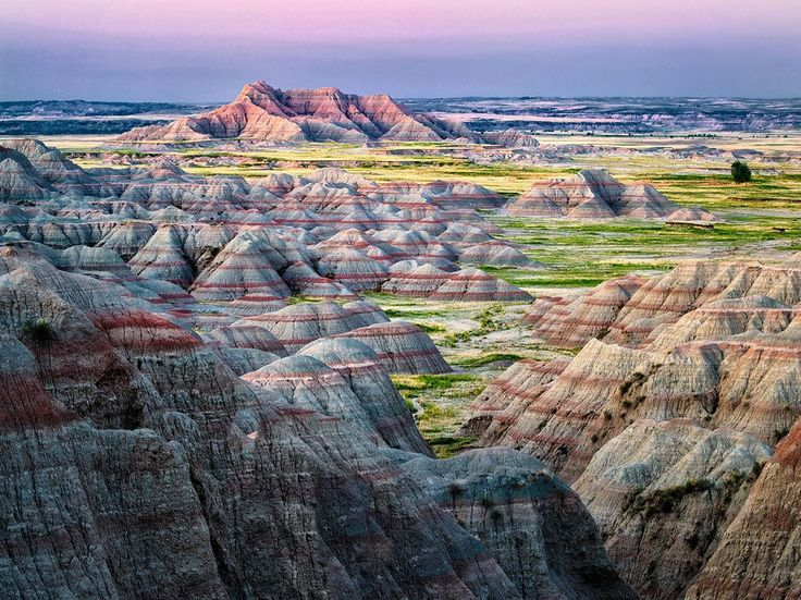 Tucked into South Dakota's southwest corner, Badlands National Park greets visitors with an otherworldly landscape of rust-colored buttes, spires, and pinnacles rising across thousands of acres. Start your road trip on the 40-mile Badlands Loop Scenic Byway, stopping at overlooks to gasp at gullies, canyons, and the occasional bison sighting. From the park, drive 90 minutes southwest across I-90 and down SD-240 to Mount Rushmore and pay homage to one of America's most iconic sights: the…