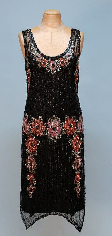 SEQUIN DECORATED NET DRESS, 1920's. Sleeveless black cotton net with a vertical black sequined stripe having floral pattern in pink, copper and silver at the neck, arm openings and waist, edges all trimmed in tiny black beads, double pointed hem and side slits.